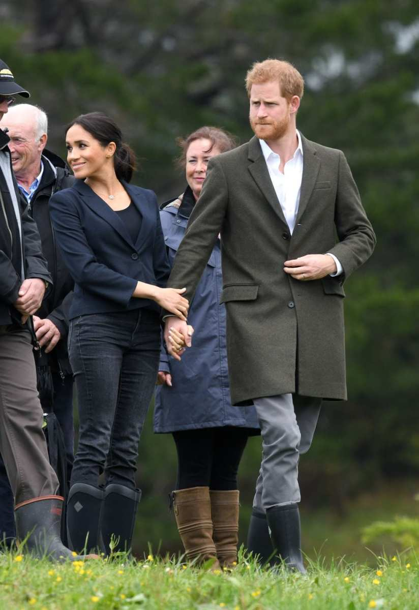 Meghan is holding Prince Harry's arm with two hands and pulling him toward her.