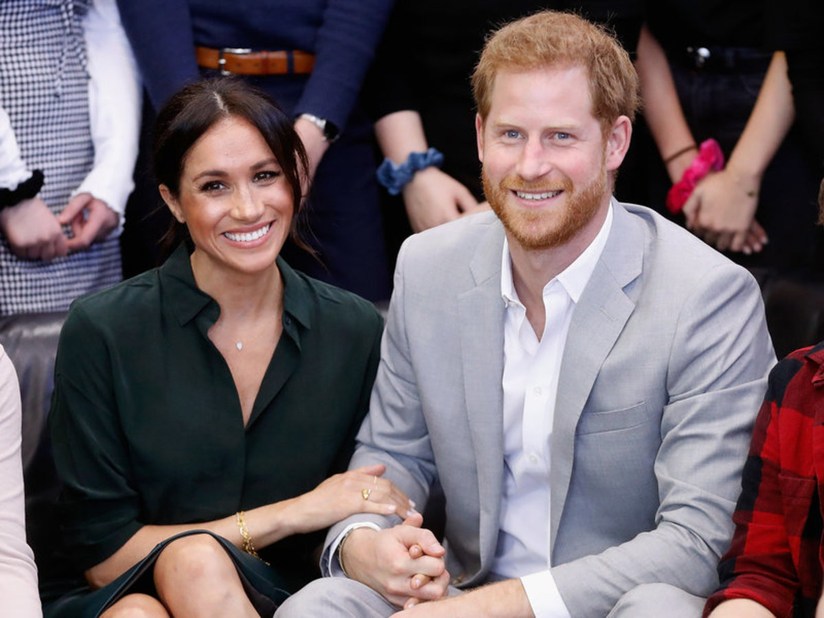 Prince Harry is holding Meghan's hand and she is holding his arm.