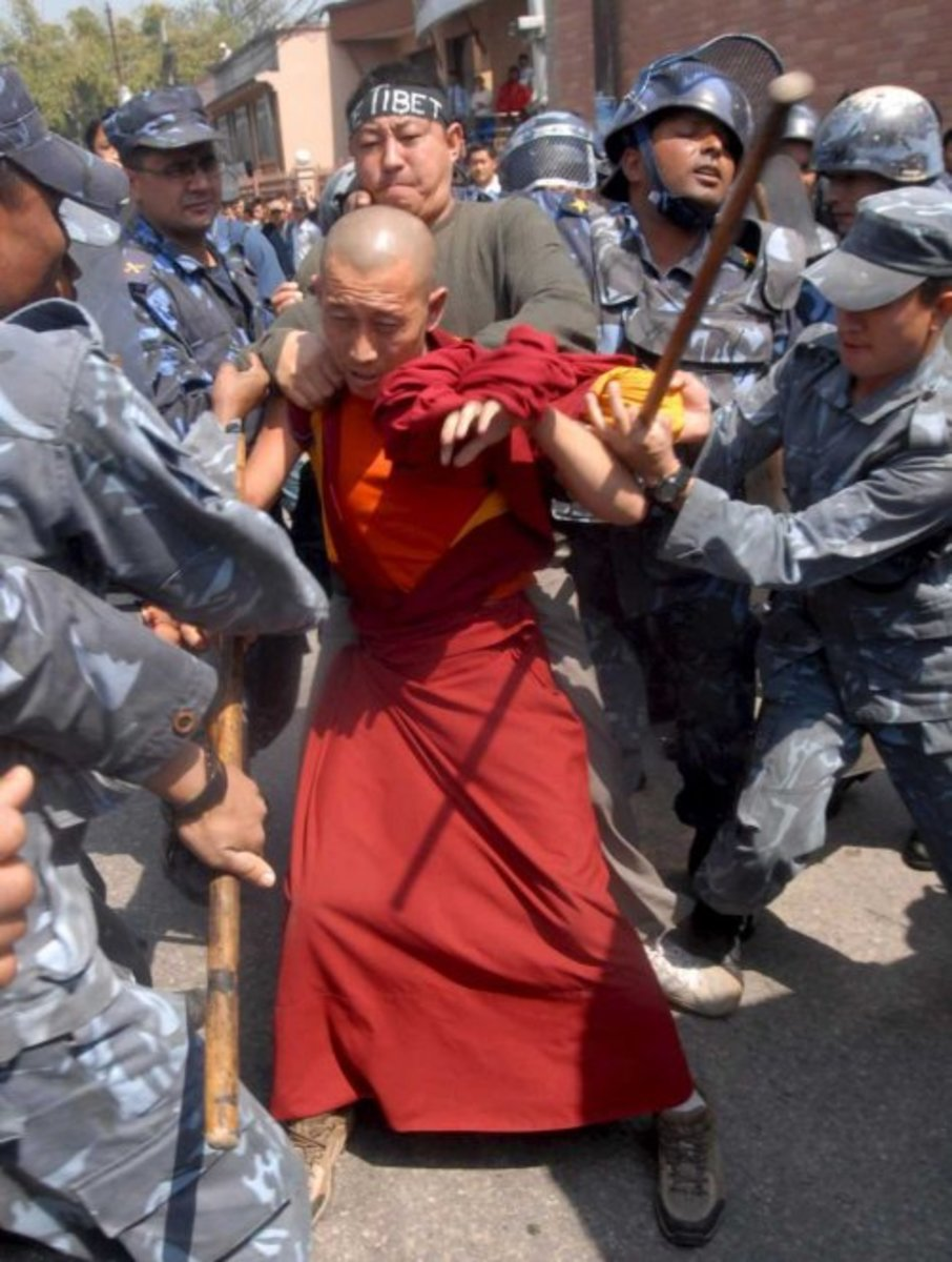 Tibetan monk struggling against Nepalese border guards.