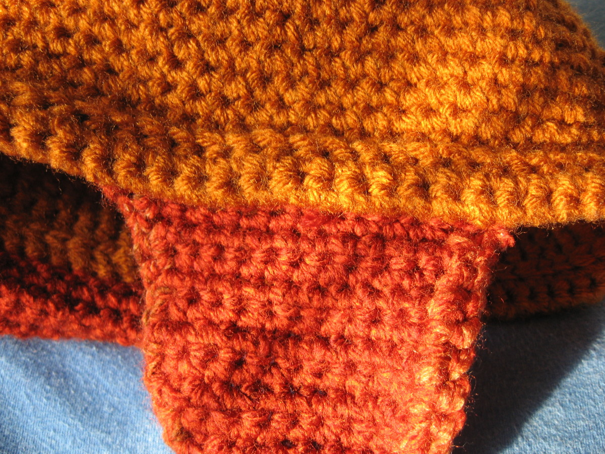 The ear flaps are attached to the inside bottom of the rolled brim.  As you can see, I also crocheted around the edge of each ear flap to  male it look nicer.
