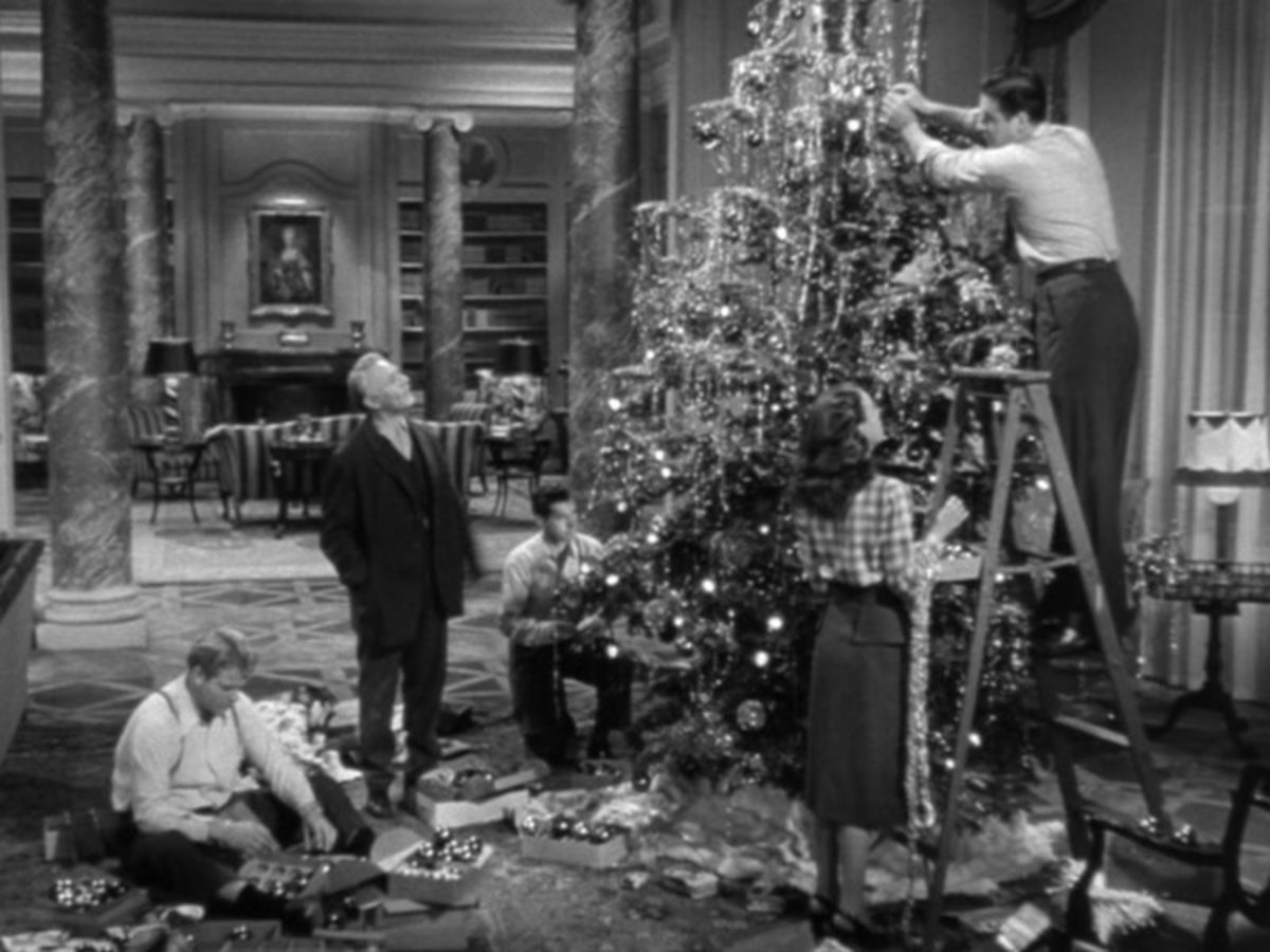 Mike watches as the squatters trim the tree in his mansion