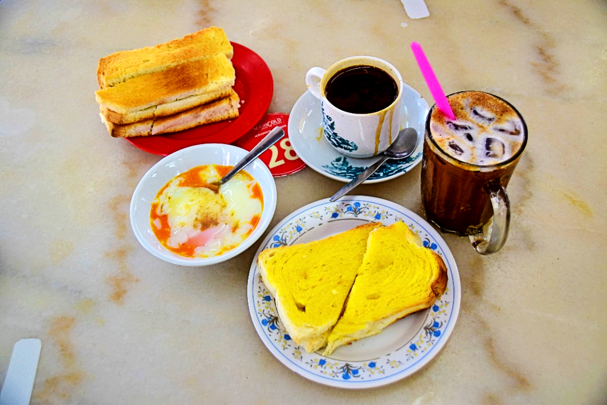 A traditional Malaysian breakfast of Toast, Half boiled eggs and Coffee.