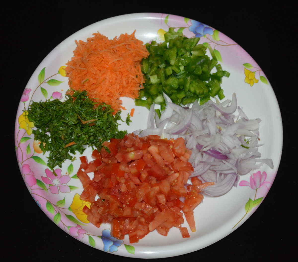 Step one: In a large mixing bowl, add chopped onions, capsicum, tomatoes, coriander leaves, and grated carrot.