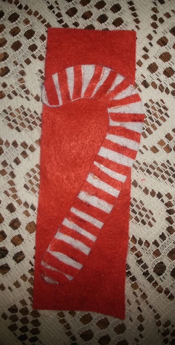 Glue candy cane on to red felt.