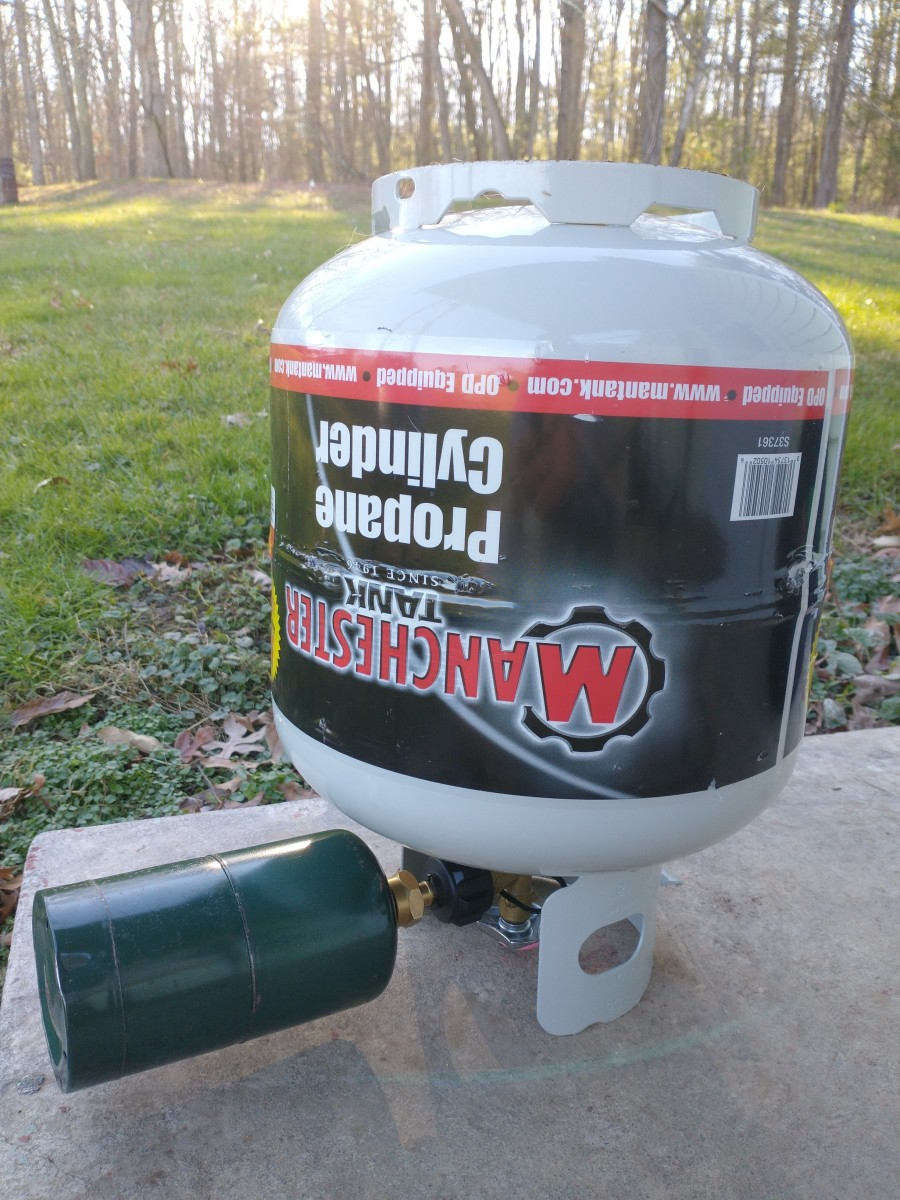 Propane bottle attached to refill adapter on a larger propane tank, ready to be refilled.