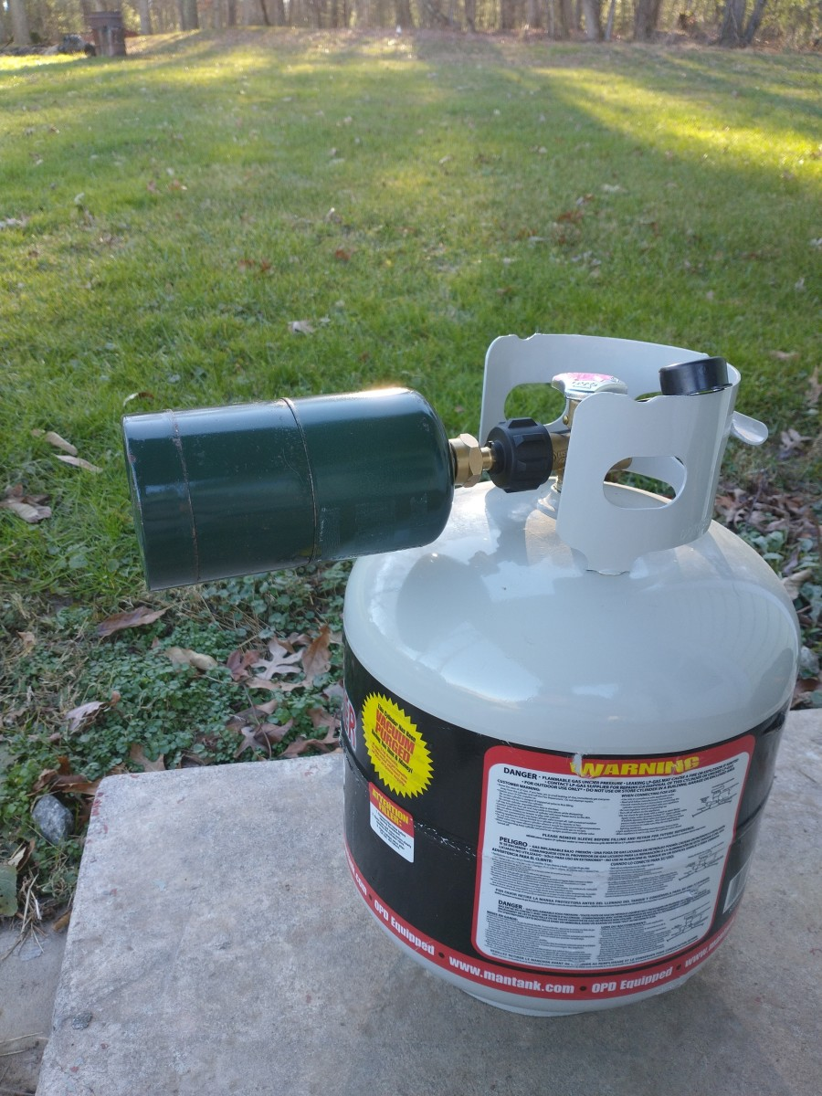 Cylinder, tank, and refill adapter connected. Don't open the valve while upright or you won't get very much propane transferred into the smaller cylinder.