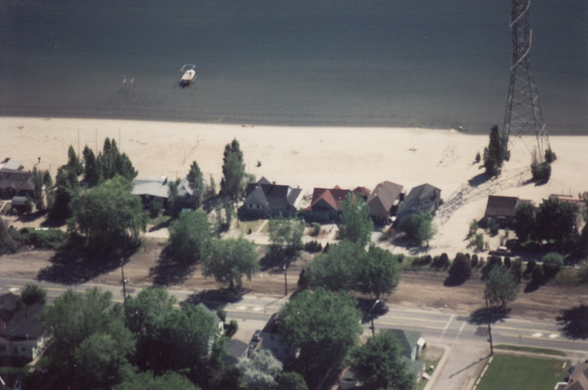Aerial photo of Beach Strip in 1990.  The brown dirt area in foreground beside Lakeshore Rd. is where the six Terry cottages used to be. Note that in this area the cottages were double stacked, and only the cottages along the beach remain in 1990.