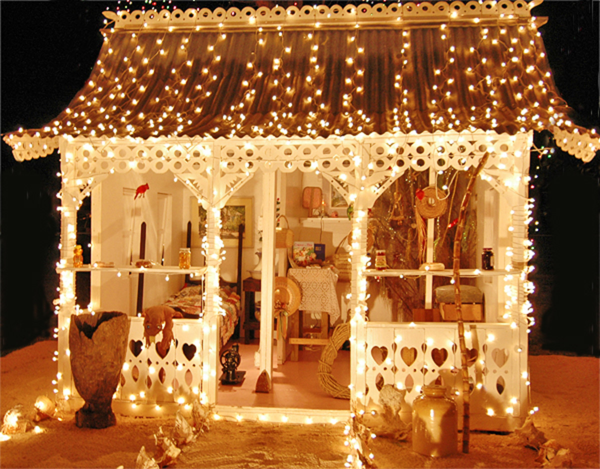Traditional Cayman home all decorated for Christmas, with lots of lights and the sandy yard.