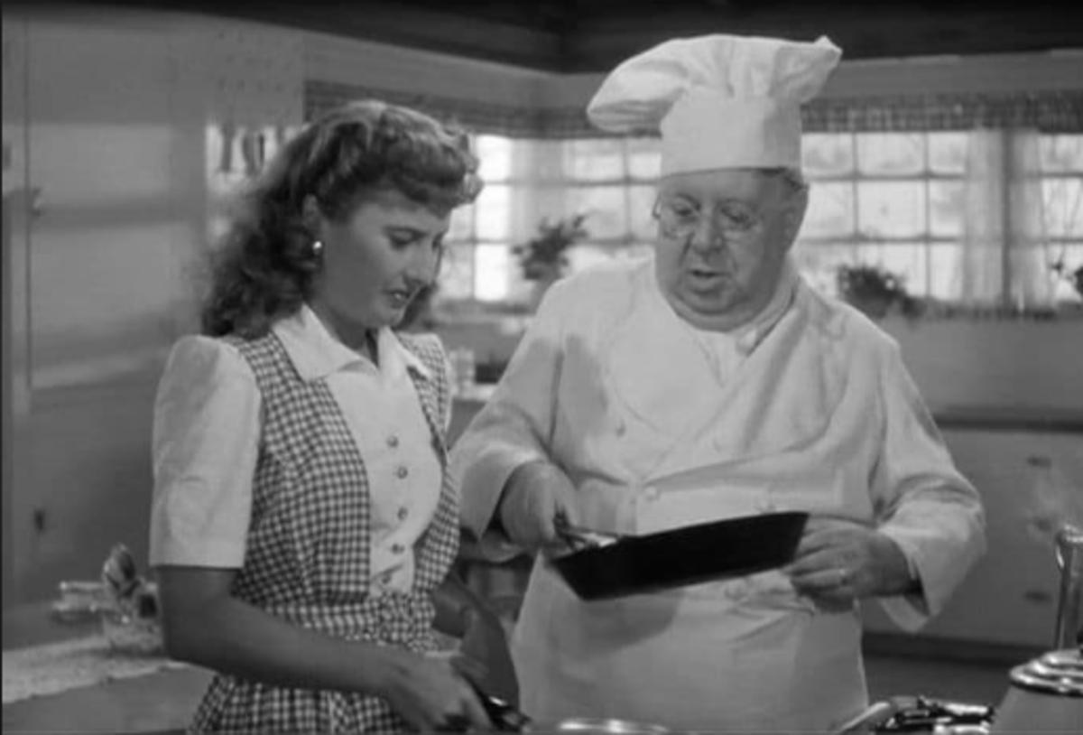 S.Z. Sakall showing Barbara Stanwyck how to flip flapjacks