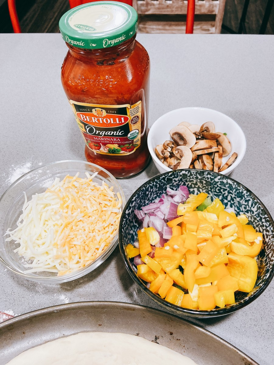 The toppings: marinara sauce, sliced veggies, and shredded cheese