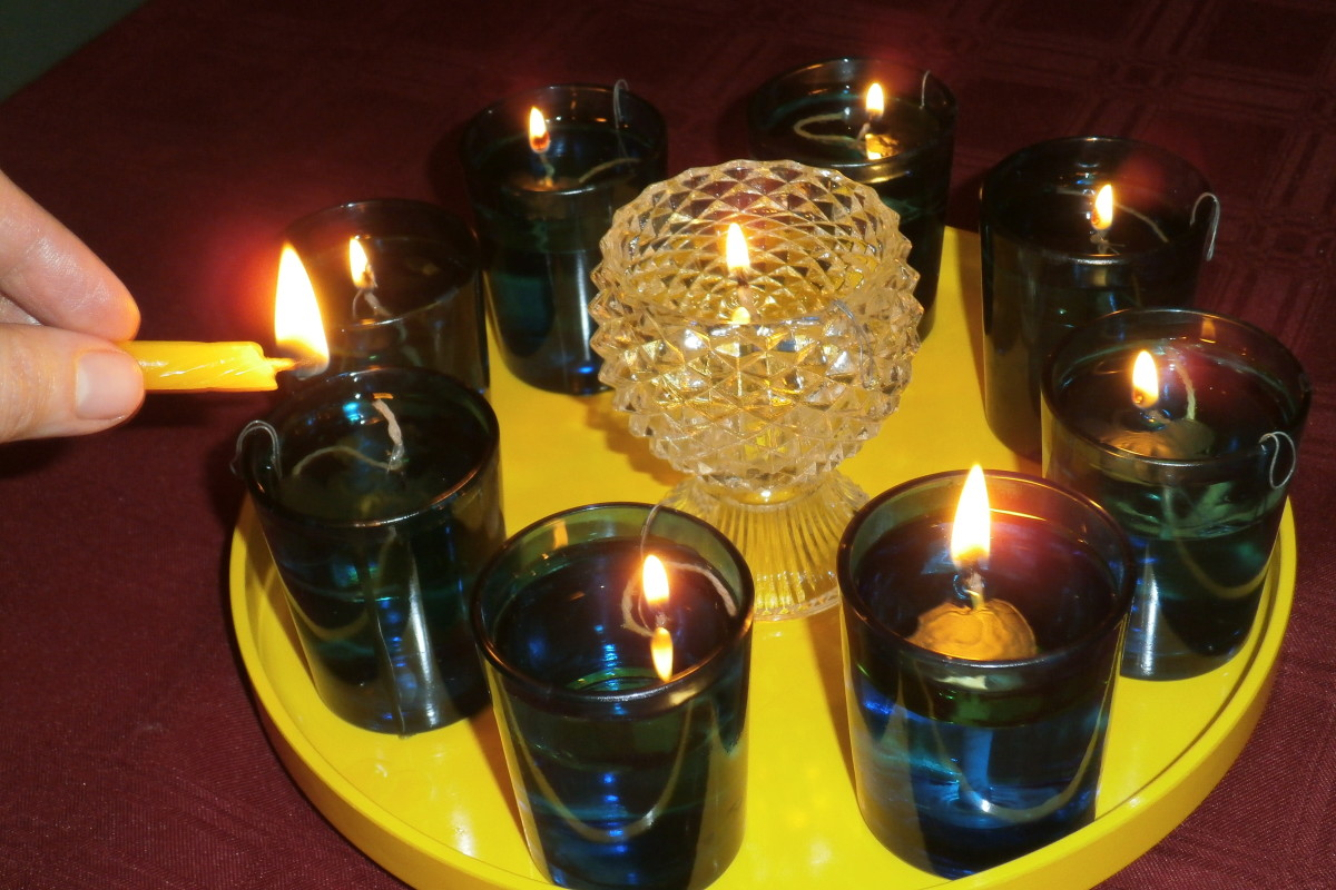 Using a handheld candle to transfer the flame from the shamash to the other oil candles