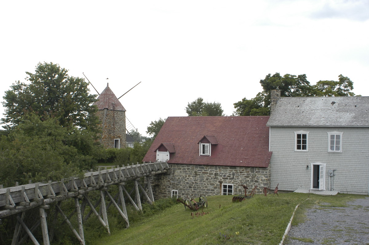 The sluice leads to the overshot waterwheel inside Alexis Tremblay's gristmill on Isle-aux-Courdes.  The windmill built by his son can be seen in the background.
