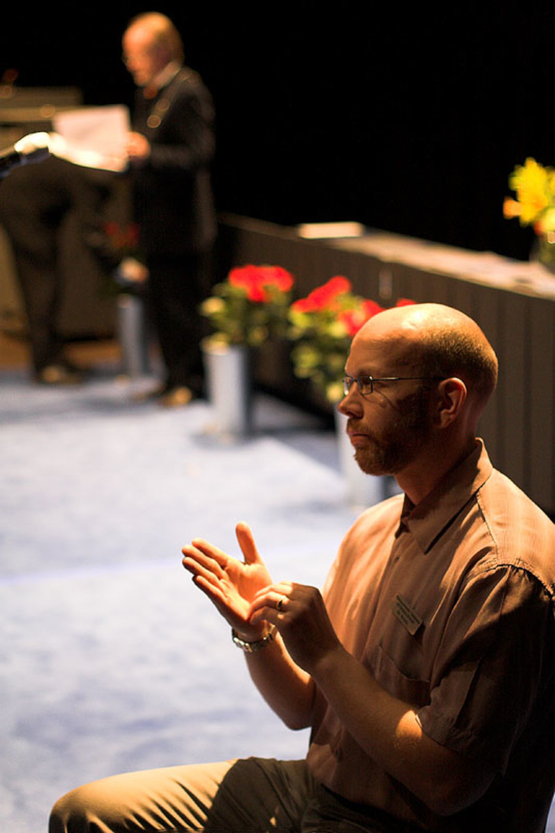 Deaf interpreters work with hearing sign language interpreters such as the man in the photo
