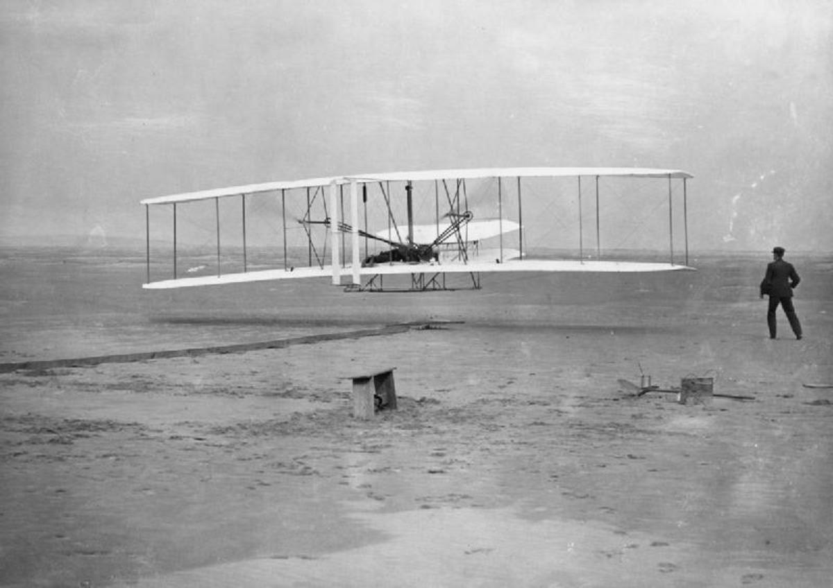 The Wright Flyer airborne during the first powered flight at Kitty Hawk, North Carolina, United States of America, 17 December 1903. Orville Wright is the pilot while Wilbur Wright runs alongside