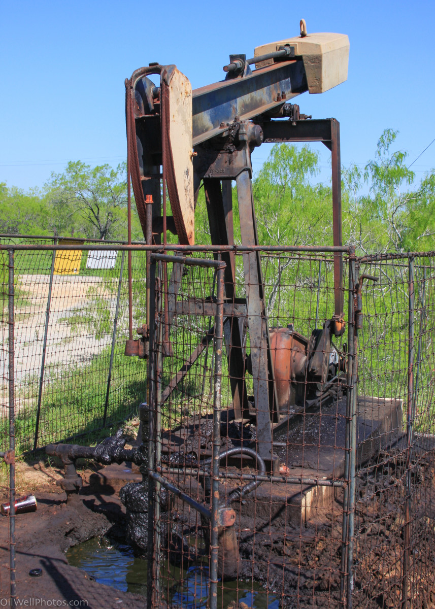 This old stripper well has gas bubbling up in a pool of oil at the base of the casing. This indicates that the casing is compromised at some point.