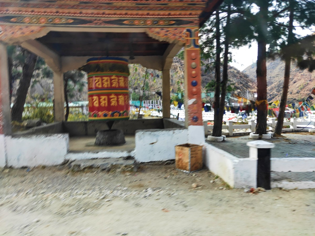 A prayer wheel adjacent to the gate