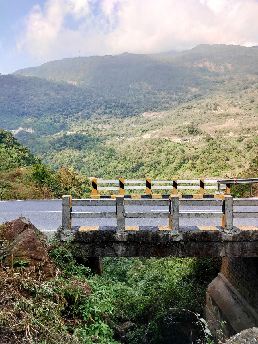 What a sight to behold - a bridge, green mountains, wide road on sunny day
