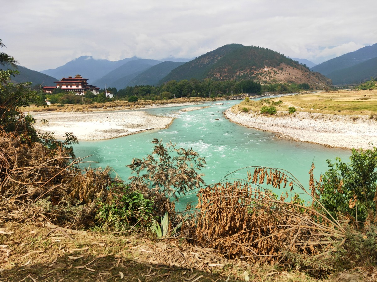 The green river, rolling hills, Dzong, the clear sky - looks like a fairyland