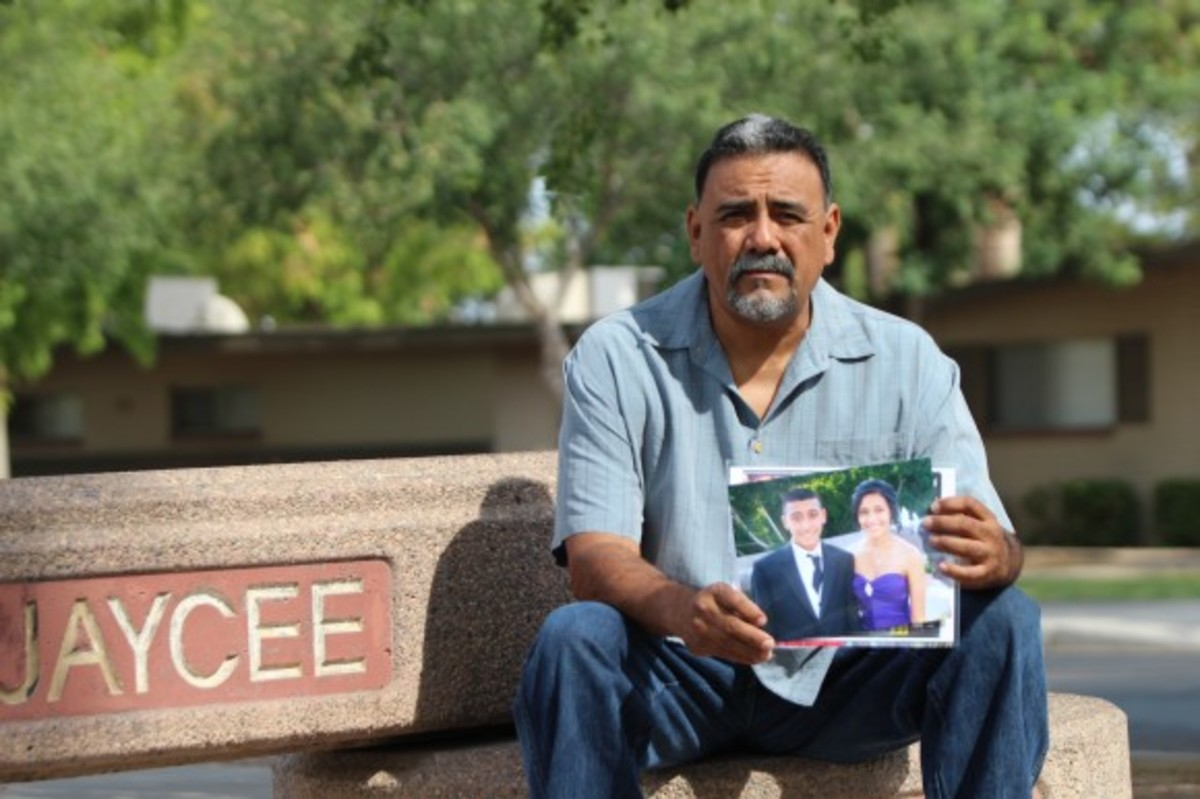 Adrienne Salinas's father Rick sitting at Jaycee Park in Tempe, Ariz., showing a picture of his murdered daughter.
