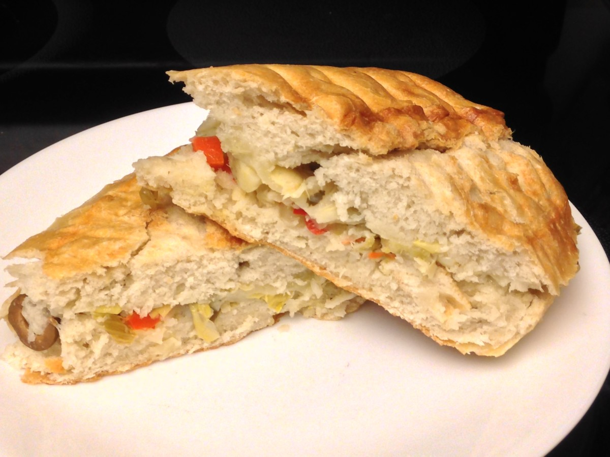 Muffaletta panini with olives, pickled vegetables, provolone, and artichoke hearts on baguette.