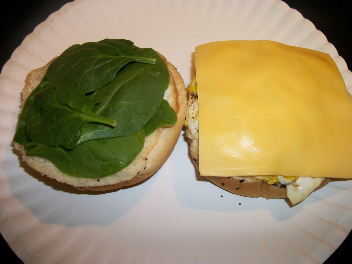 Fried egg sandwich with cheese and spinach on onion roll