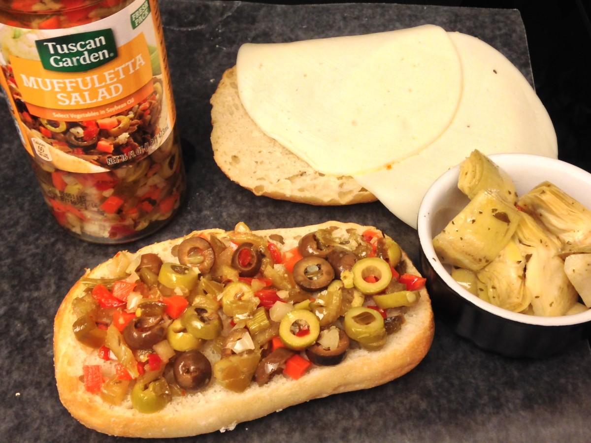 Assemble Muffaletta with muffuletta salad, artichoke hearts and provolone