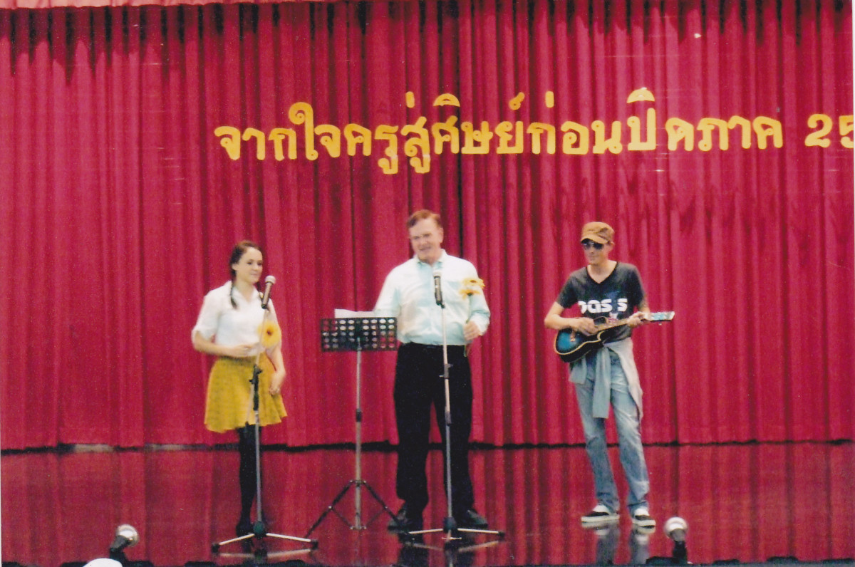 The author in the middle performing at a school end of the year party for students.