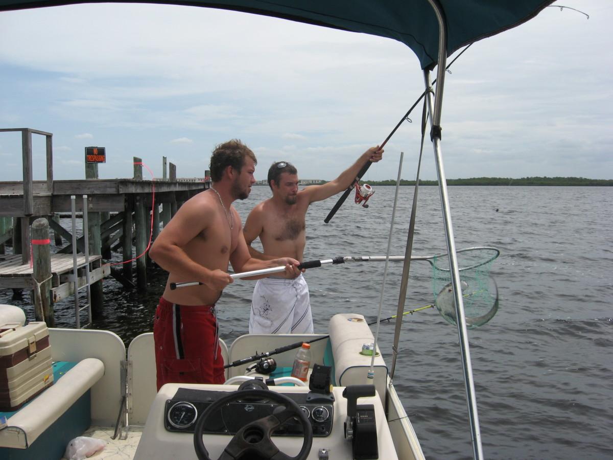Cory and Jade land a small shark while flats fishing.