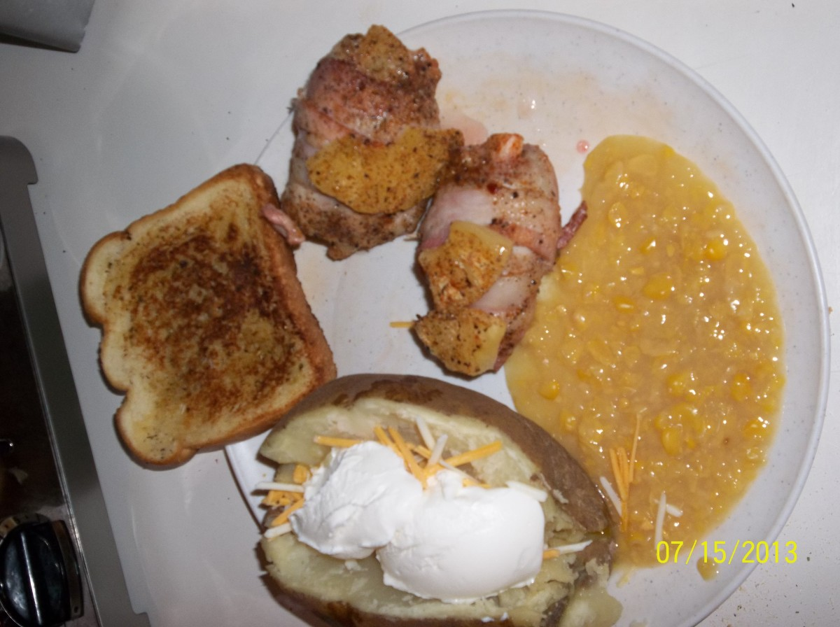Bacon wrapped chicken thighs stuffed with pine apple and cherries shown served with a fully loaded baked potato, cream corn and grilled herb toast