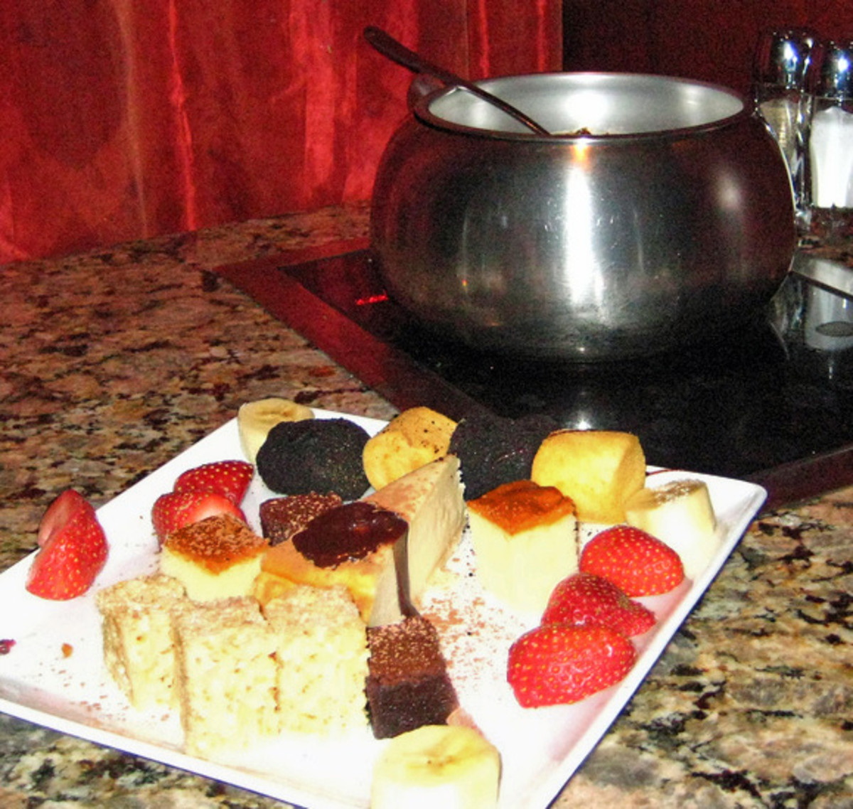 A pot of warm dark chocolate fondue with strawberries and cake squares for dipping