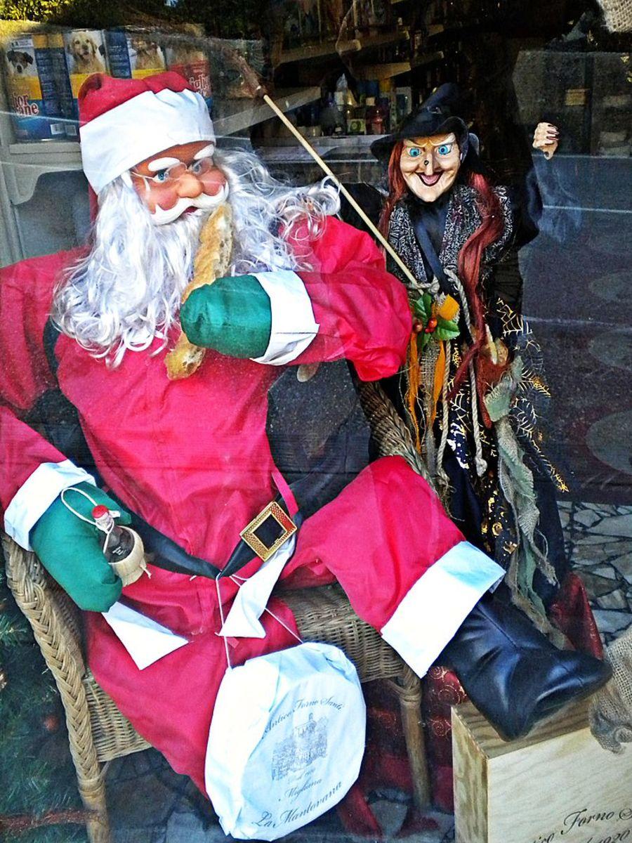 La Befana next to Santa. Store window decoration in Italy.