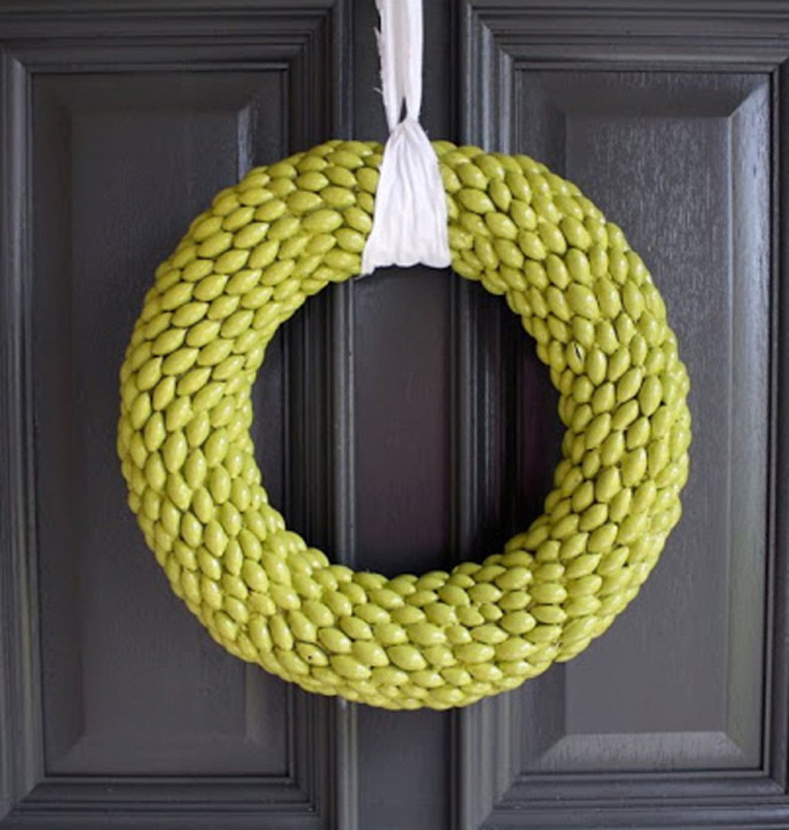 The chartreuse wreath is painted. These caps were taken off the acorns.  It is made the winter wreath with a ribbon on the front door.