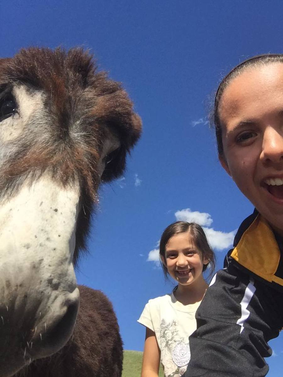 Our daughter Noelle takes a selfie with our daughter Grace and a friendly burro