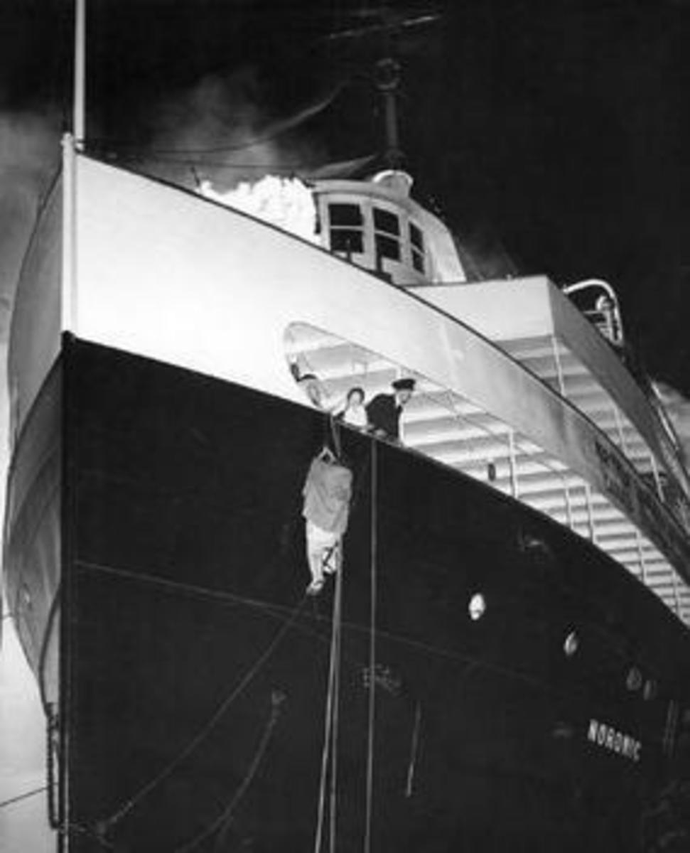 A passenger escapes down a rope with the blaze in the background.