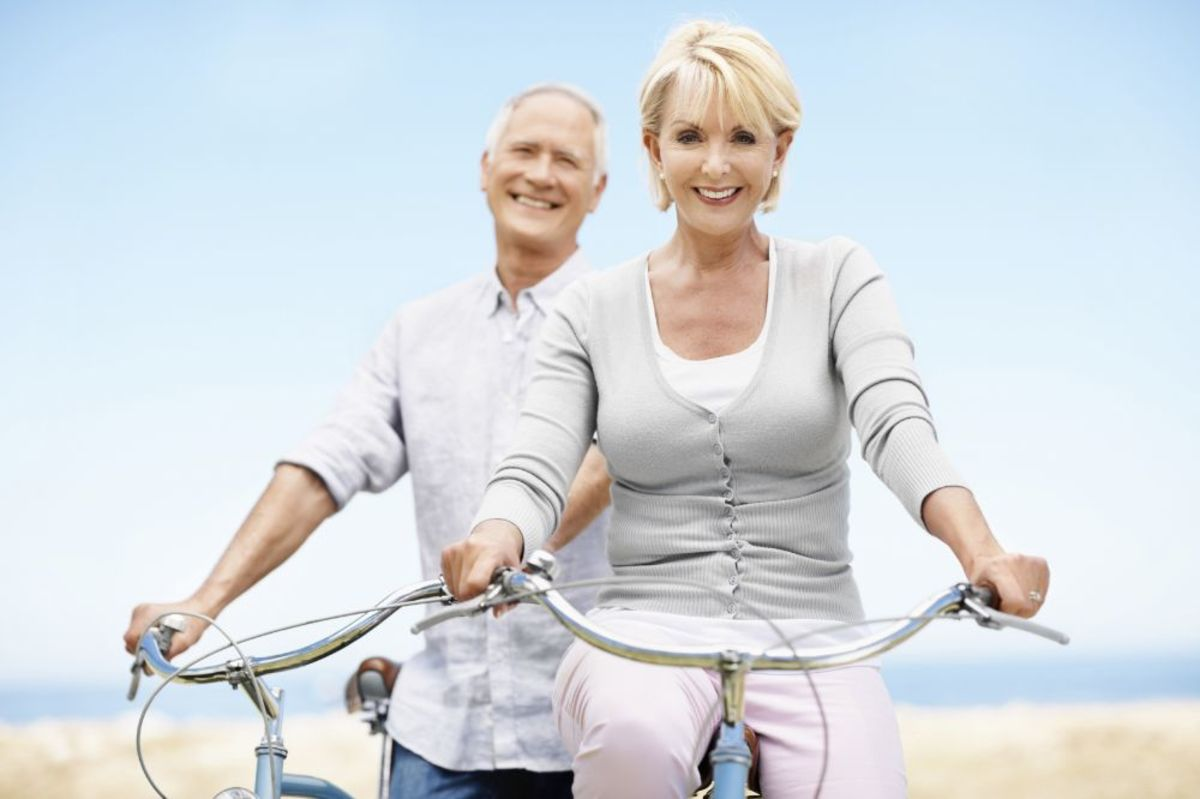 attractive senior couple in white and grey bicycling