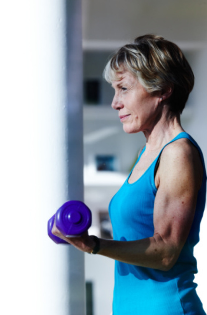 attractive older female with arm muscles showcased holding a purple barbell