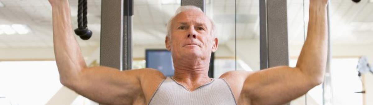 senior man with grey hair lifting weights in white tank top