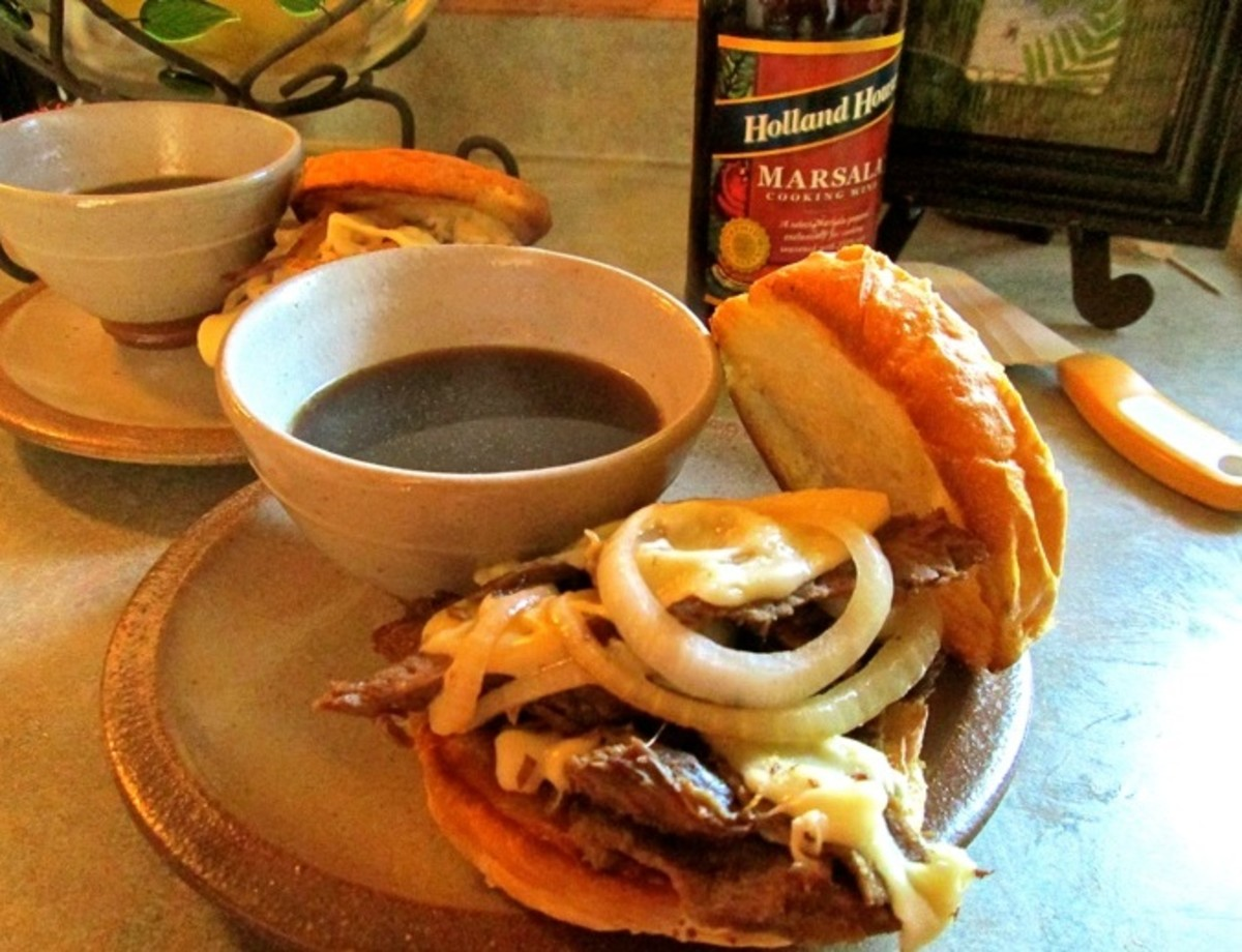 French Dip Au Jus Sauce and Sandwiches On Plates For Dinner