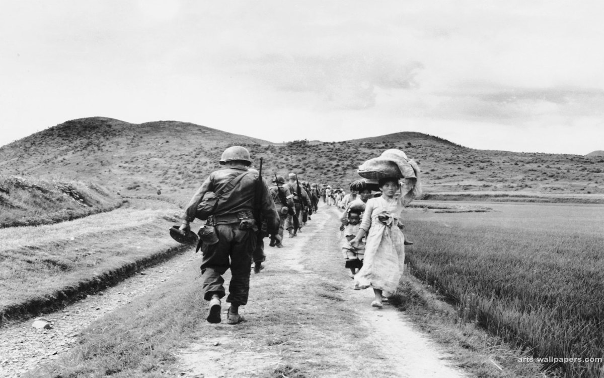 WHILE AMERICAN TROOPS HEAD NORTH, AN ENDLESS STREAM OF KOREAN CIVILIAN REFUGEES WALK SOUTH TO ESCAPE THE SOCIALIST ARMY
