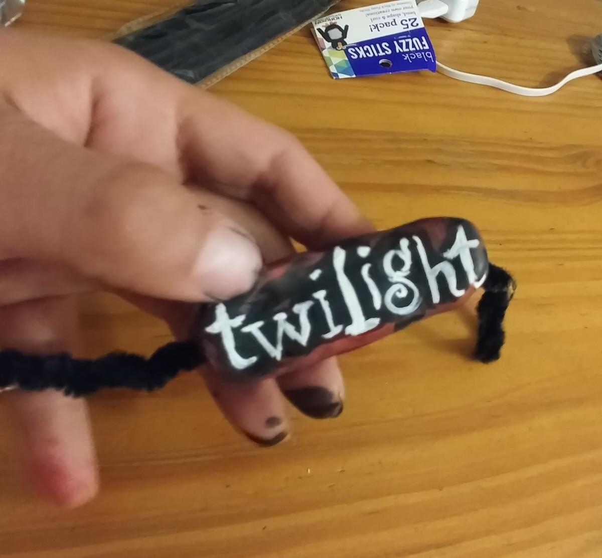 Glue the Twilight emblem onto the fuzzy sticks.