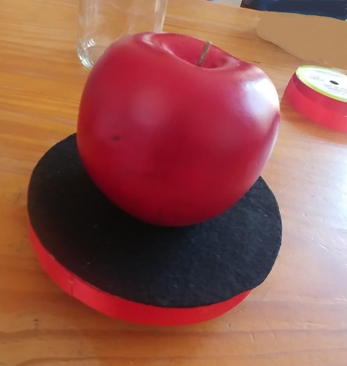 Glue red apple on the felt.