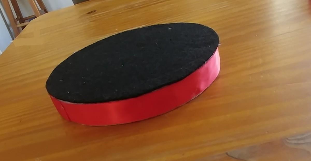 Glue black felt onto the foam circle.