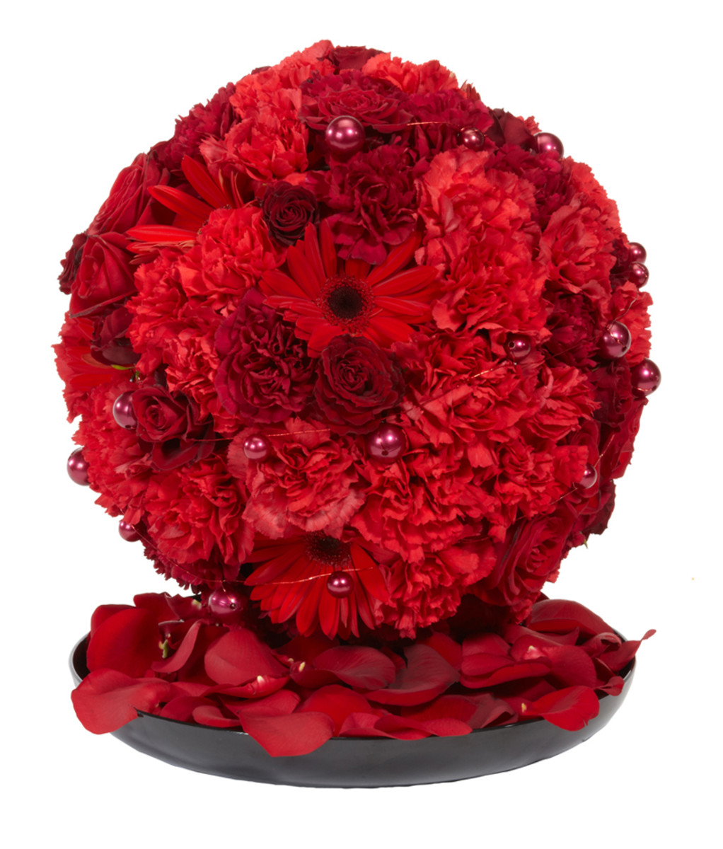 A foam sphere, filled with different red flowers and placed on a mirror.