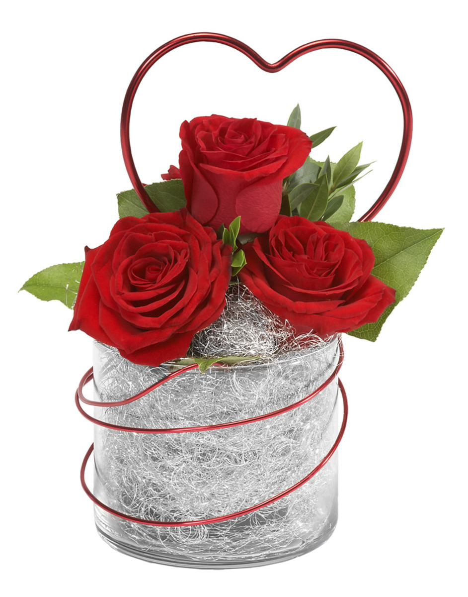 Another reason to have some silver angel hair and red wire in your flower arranging tool kit. Add three red roses and a few sprigs of green, all you need is a small glass and you have a quite simple arrangement.