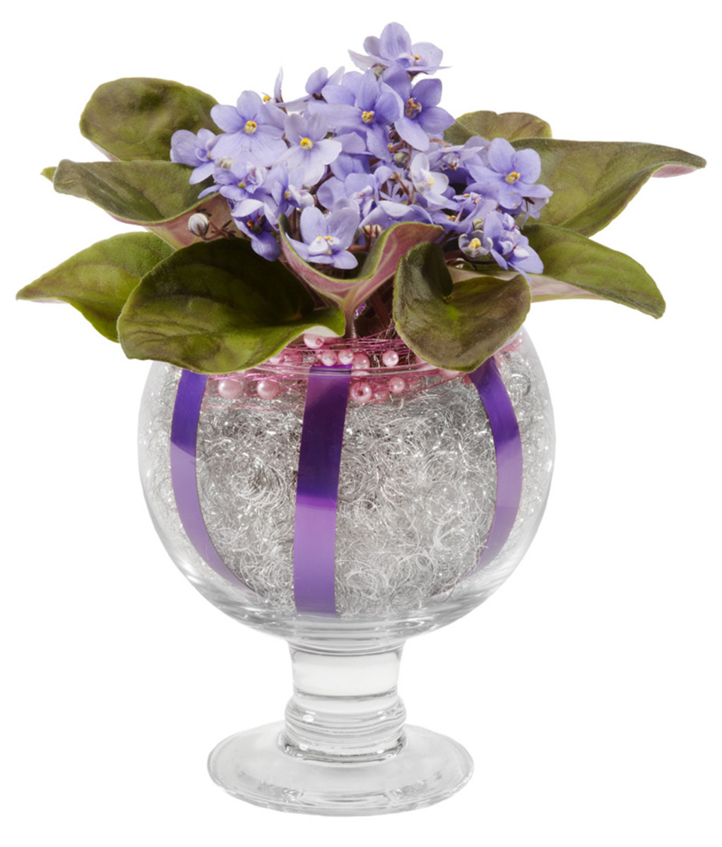 An African violet plant, the pot covered in angel hair wire, and the edge bound in pink beaded wire. large bands of purple wire line seven inch vase.