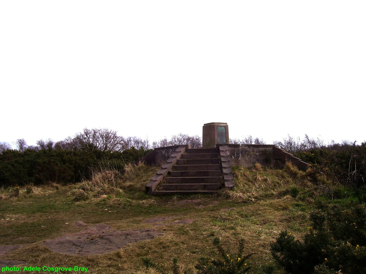 The stone plinth displays a bronze map of Wirral.