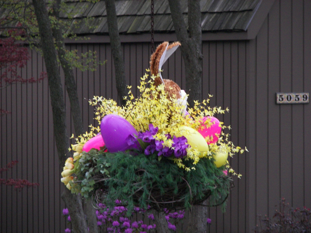 Holiday Hanging Basket Colorful Exterior Easter Decoration with yellow forsythia and pink flowers and a purple egg