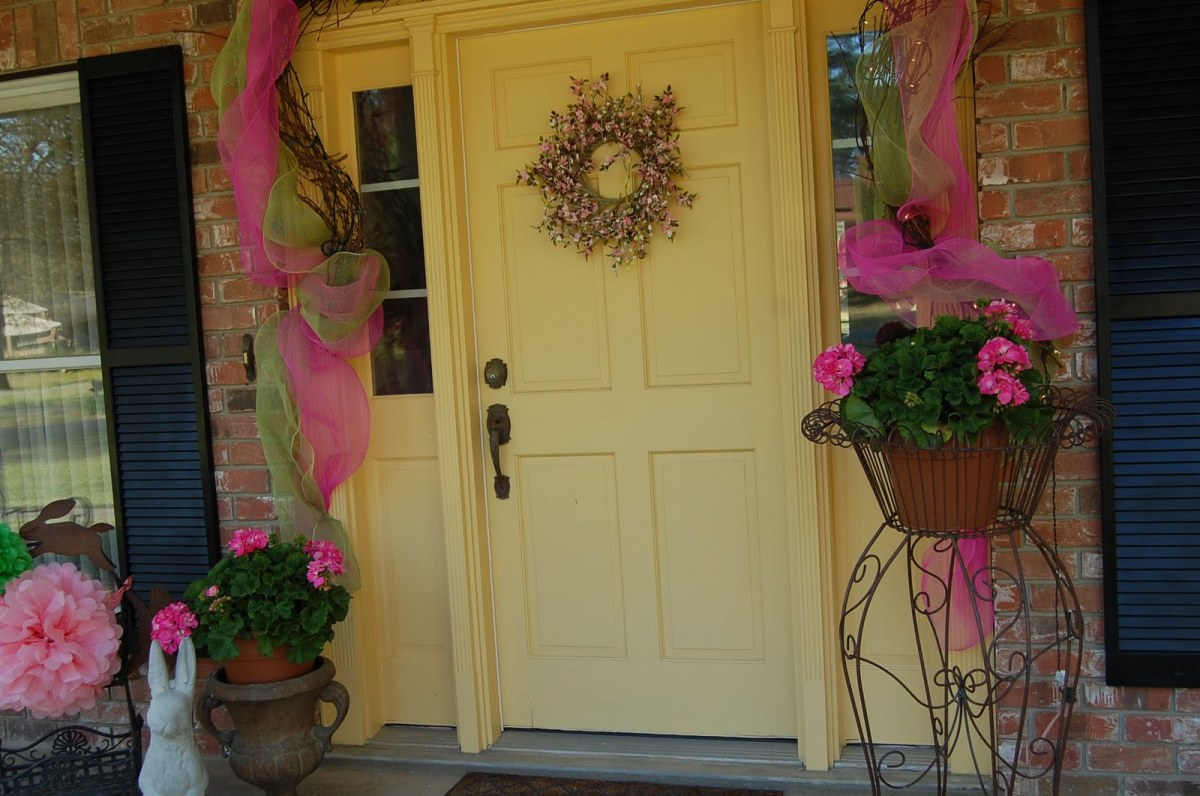 Front Door with Easter Decorations on a Yellow Door with two side planters decorated for the holiday