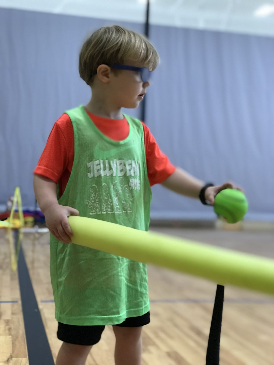 Boy in green hits ball off air tee