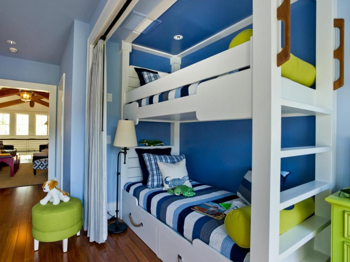 Cozy nook bunks decked with blue, green and dapper stripes with under-bed storage drawers.
